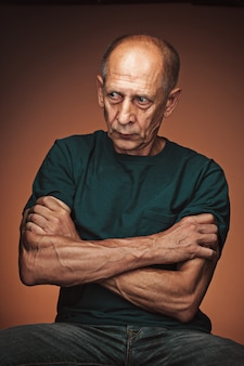 Worried mature man sitting with arms crossed