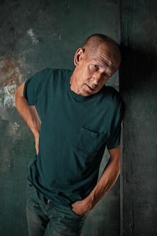 Обеспокоенный зрелый мужчина, стоящий в студии