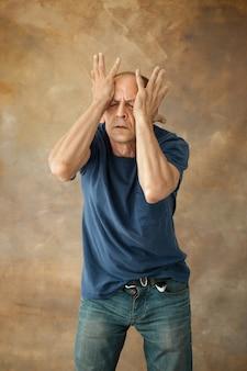 Uomo maturo preoccupato che tocca la sua testa e che pensa su.