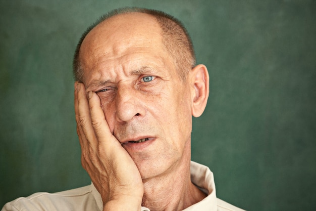 Worried mature man touching his head and thinking on.