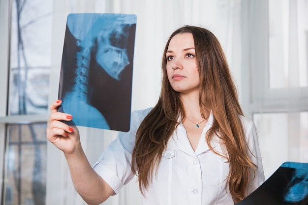 환자의 xray 샷 걱정 된 의료 노동자입니다. 병원에서 여성 의사는 인간의 스컬 뢴트겐을 검사합니다. 의학 서비스 머리 desease 건강 관리 개념.