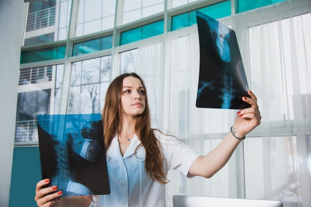 Worried medical worker with patient's xray shot. female doctor at clinic examine human scull roentgen. medicine service head desease healthcare concept.