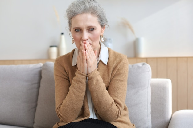 居間のソファーに座っている心配中年の女性。