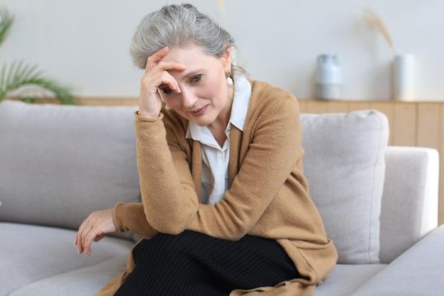 거실 소파에 앉아 걱정하는 중년 여성.