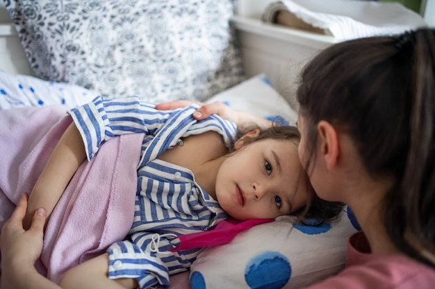 自宅のベッドで病気の小さな娘の世話をしている心配している母親、コロナウイルスの概念。