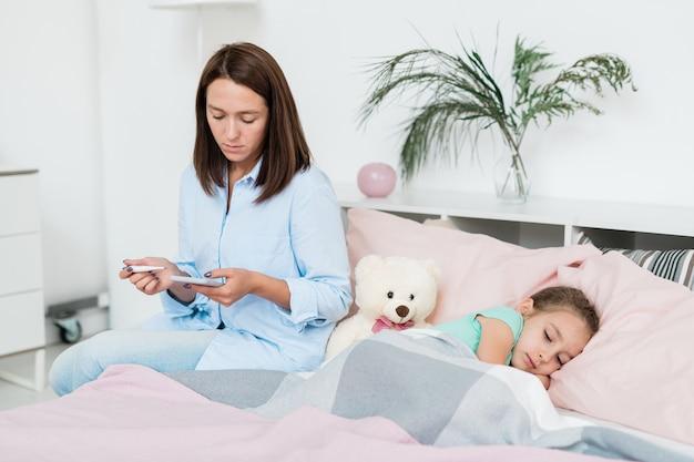 彼女の病気の小さな娘がベッドの上に座っていると電話の医者に行く温度計で心配する母親