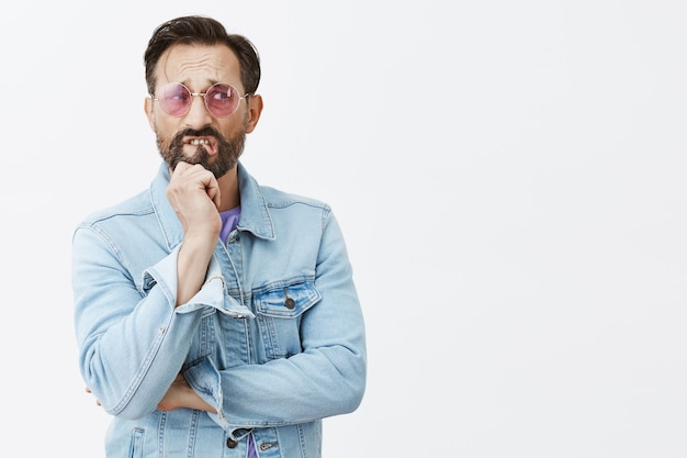 Worried and nervous bearded mature man posing