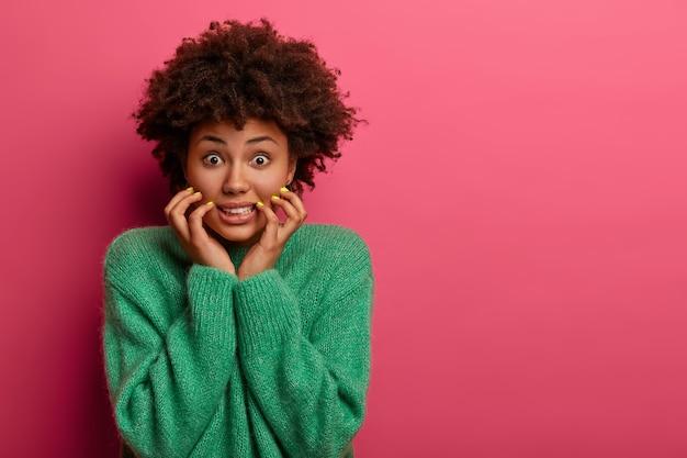 心配している神経質な女性は歯を食いしばって、顔に手を保ちます