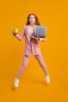 心配している素敵な赤毛の成功した女性リーダーがラップトップとコーヒーを運んで空中にジャンプし、黄色の背景、コピースペースで隔離された高速急いで会議を実行します