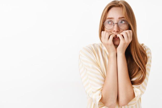 Preoccupato in preda al panico carina e timida ragazza rossa insicura con gli occhiali che guarda in alto tremante per la paura mordere le unghie tremante sensazione di paura