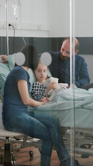 건강 검진 중 질병 전문 지식을 기다리는 아픈 소녀 딸과 함께 앉아 걱정하는 부모 ...