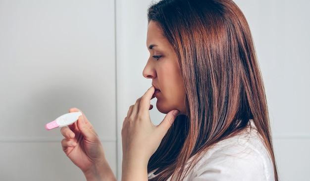 Обеспокоенная беременная женщина, смотрящая на тест на беременность