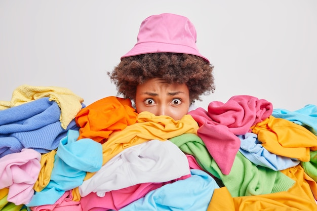 Worried puzzled woman cluttered with unfolded mixed up clothes raises head drom heap of unfolded multicolored laundry