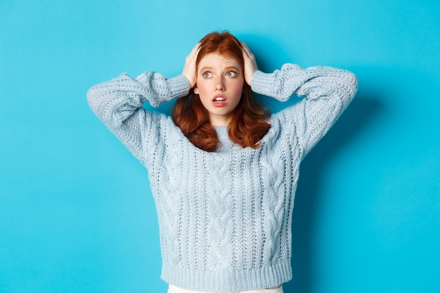 Взволнованная рыжая девушка стояла ошеломленная, держась за голову в панике и глядя налево на логотип, встревоженно стоя на синем фоне