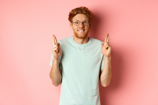 Worried redhead man waiting for results, expecting something with fingers crossed, biting finger and looking at something risky, standing over pink background.