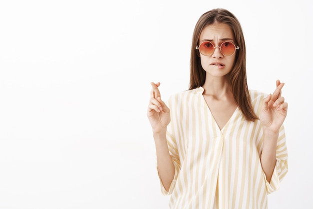 Worried sad good-looking stylish woman in trendy yellow striped blouse and sunglasses biting lip frowning and crossing fingers for good luck while making wish and waiting hopefully for result