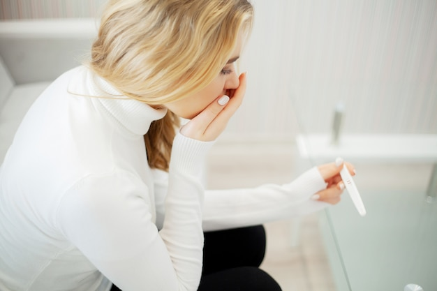 Worried sad woman looking at a pregnancy test after result