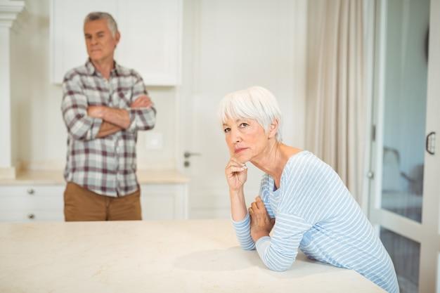Worried senior couple in kitchen