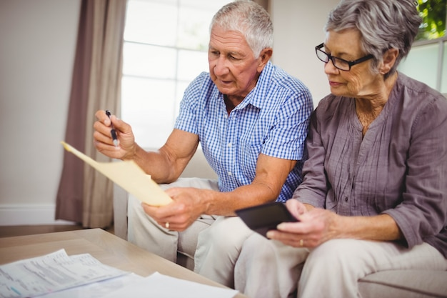 Worried senior couple sitting on sofa and calculating bills in living room