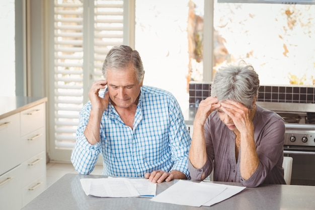 Worried senior couple with documents in kitchen