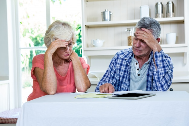 Worried senior couple with documents at table
