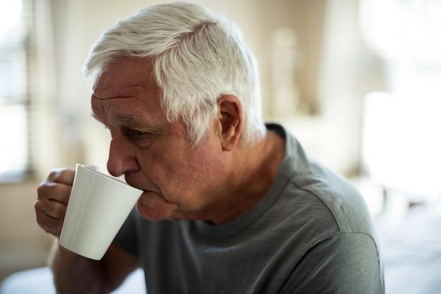 Обеспокоенный старший мужчина пьет черный кофе в спальне дома