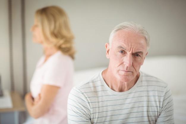Обеспокоенный старший мужчина, сидящий на кровати
