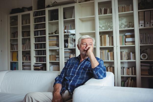 Взволнованный старший мужчина сидит на диване
