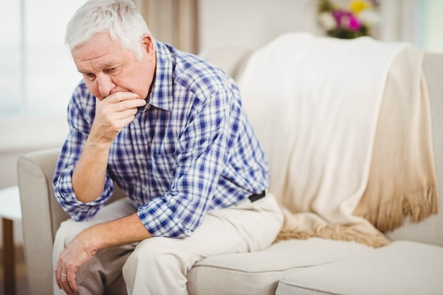 Worried senior man sitting on sofa in living room
