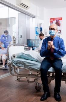 Обеспокоенный пожилой мужчина с маской для лица от covid-19 в больнице для консультации с врачом