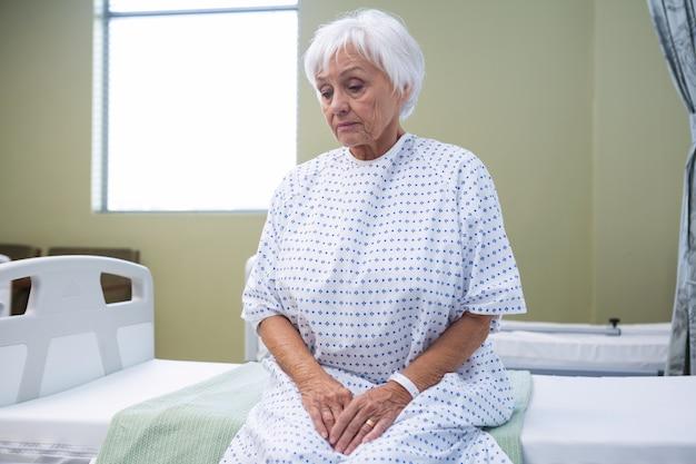 ベッドの上に座って心配するシニア患者