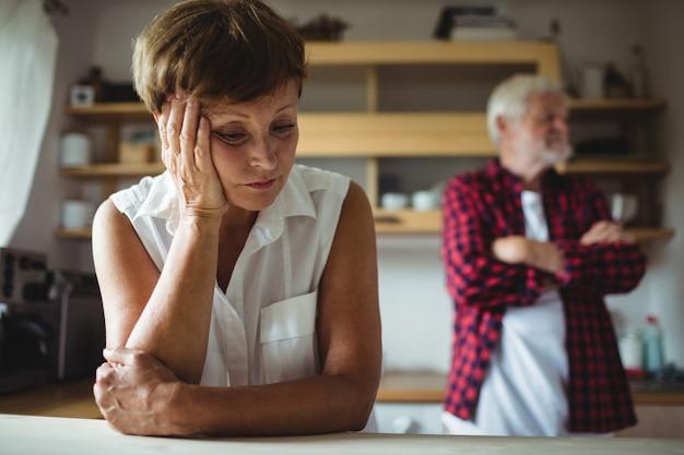 Потревоженная старшая женщина полагаясь на таблице