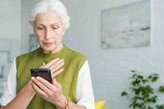 Worried senior woman looking at smartphone