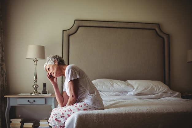 Потревоженная старшая женщина сидя в комнате кровати