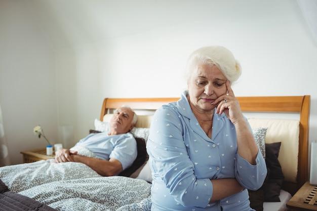 Потревоженная старшая женщина сидя на кровати