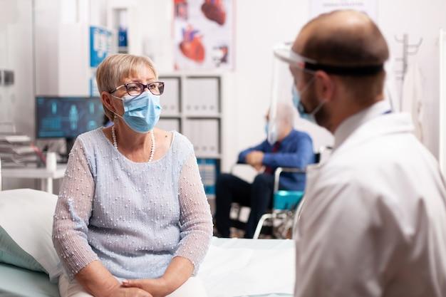 相談の過程で医者を見ているフェイスマスクを持つ心配している年配の女性