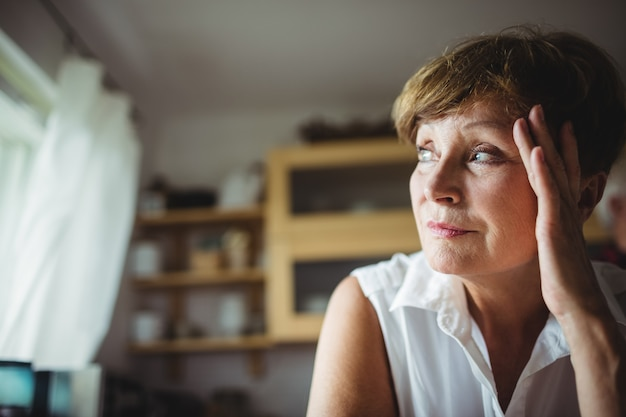 Worried senior woman with hand on forehead