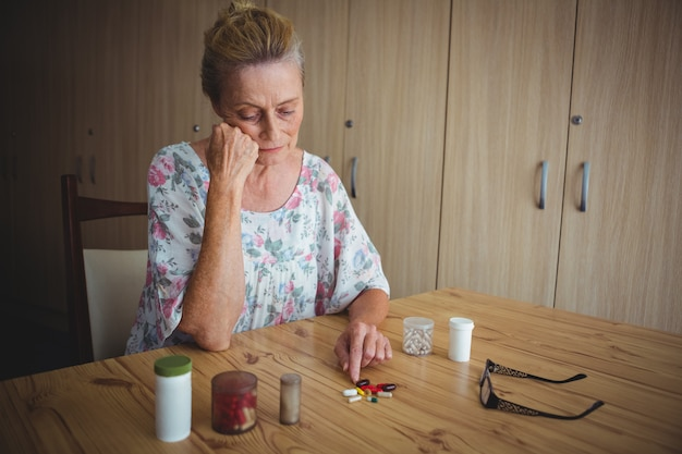 Worried senior woman with medics on the table