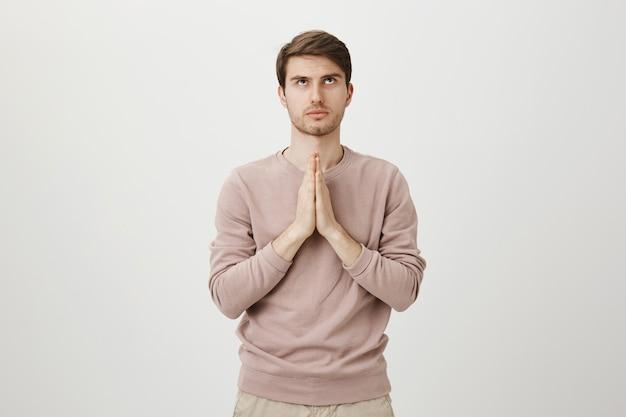 걱정되는 심각한 표정의 남자가 하나님을기도하고, 손을 잡고 간청하고 올려다 보았습니다.