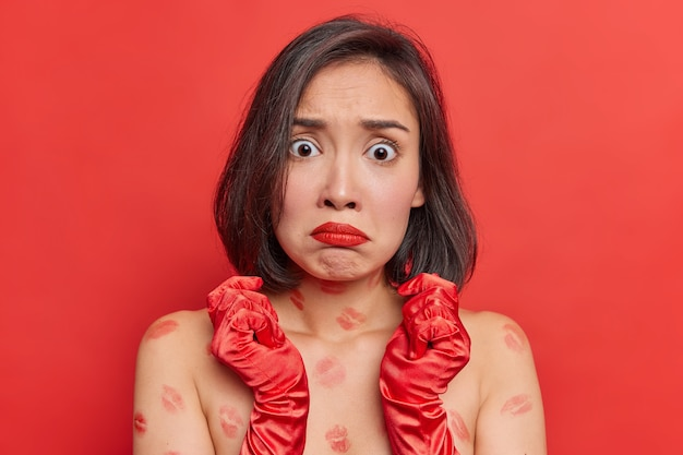 Worried shocked alarmed asian woman with dark hair ourses lipps stares at camera stands bare shoulders wears red lipstick long gloves poses indoor against vivid studio wall