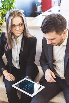 Обеспокоенная напряженная женщина-стартап показывает свой проект инвестору. деловая встреча, планшетный пк в руках, макет