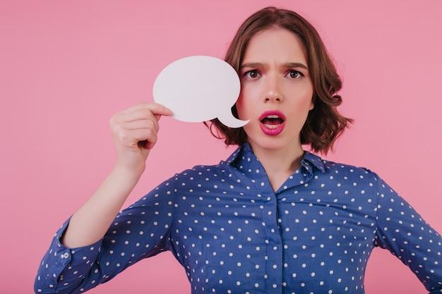 何かを考えている青い服装で心配しているスタイリッシュな若い女性。ピンクの壁に隔離された壮大な神経質な女の子。