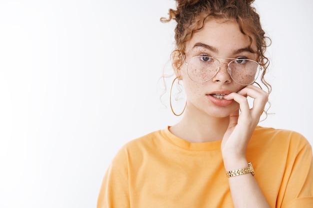 손톱을 물어뜯는 걱정스러운 10대 소녀는 투명한 안경 주황색 티셔츠를 입고 확신이 없는 흰색 배경에 불안해 보이는 불안한 표정으로 숙제를 하는 것을 잊었다