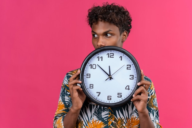 Preoccupato e premuroso giovane uomo dalla carnagione scura con i capelli ricci nelle foglie camicia stampata che tiene l'orologio da parete che mostra il tempo mentre guarda di lato su uno sfondo rosa