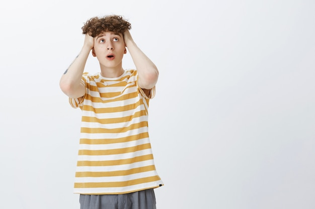 Worried and troubled teenage guy posing against the white wall