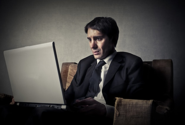 Worried unhappy man surfing on the internet