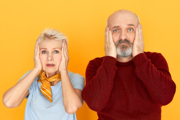 Worried unhappy mature female and bald unshaven senior male holding hands on their cheeks, having surprised shocked looks