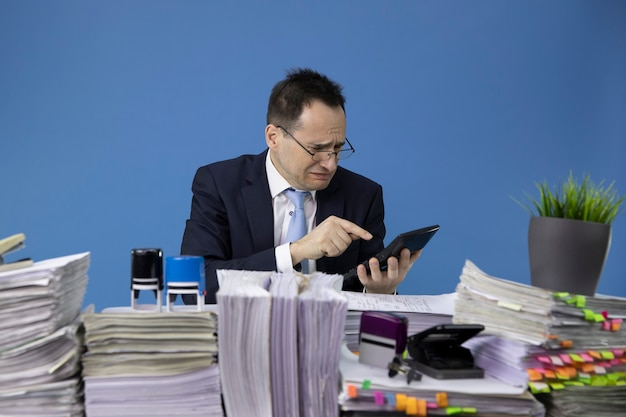 Worried weeping businessman considers losses on calculator sitting at table with piles of papers in office