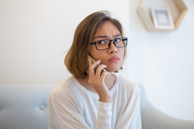Worried woman calling on smartphone on sofa at home