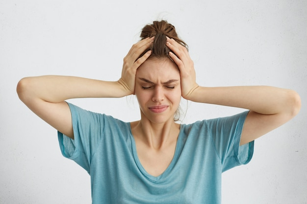 Взволнованная женщина, закрывая глаза руками на голове, испытывает головную боль